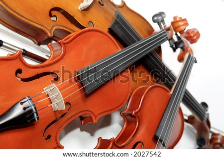 Three violins on white background. Soft focus. The Hard light. - stock photo