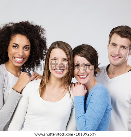 Three vivacious beautiful laughing girls with a young male friend posing close together on a grey studio background, upper body portrait