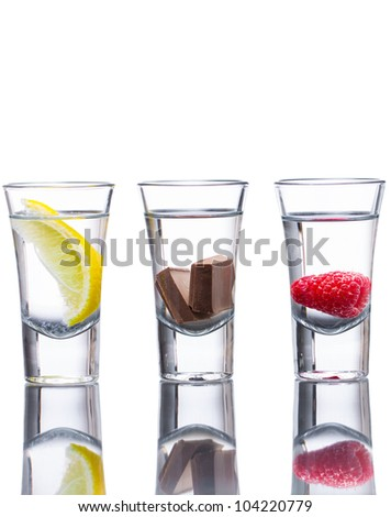 Three vodka shots flavored with raspberry, lemon, and chocolate. Reflection in table and isolated on white. - stock photo