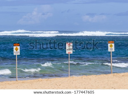 Three warning sign no swimming and strong currents in treacherous winter waters on Tunnels Beach in Kauai Hawaii - stock photo