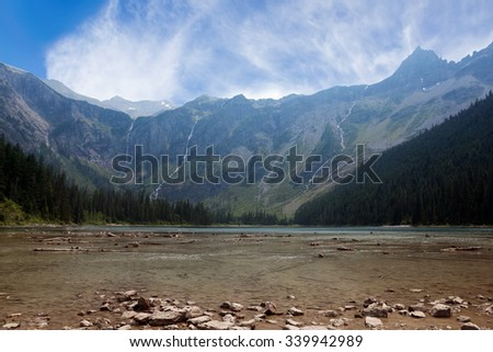 Three  waterfalls cascading  down steep mountain sides into Avalanche Lake, Glacier National Park - stock photo