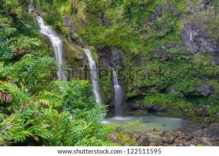 Three waterfalls in a lush tropical setting along the Road to Hana in Maui, Hawaii - stock photo