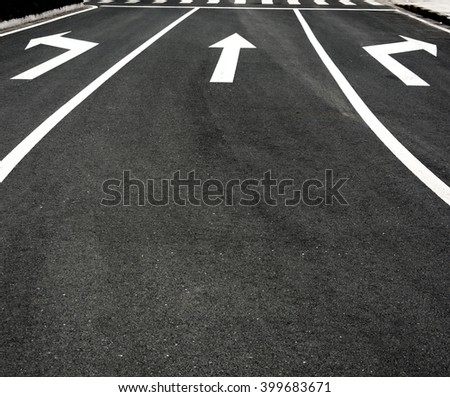 Three way arrow symbol on a black asphalt road surface - stock photo