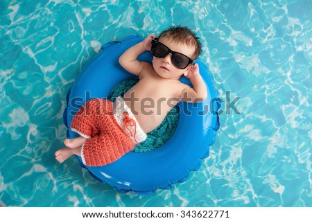 Three week old newborn baby boy sleeping on a tiny inflatable swim ring. He is wearing crocheted board shorts and black sunglasses. - stock photo