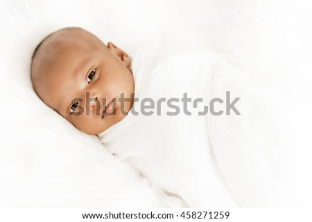 Three weeks old baby sleeping on white blanket cute infant newborn lying down close up shot eyes open