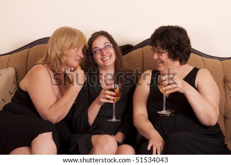 Three well dressed and diverse woman socializing with wine. - stock photo
