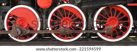 Three wheels of steam locomotive on rails closeup  - stock photo