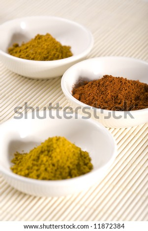 three white bowls filled with curry, cayenne pepper and turmeric, cayenne in focus