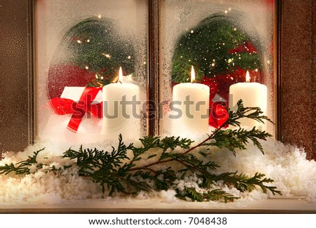 Three white candles in a frosted window - stock photo