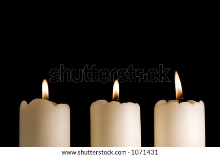 Three white candles lined up saucer isolated on black - stock photo