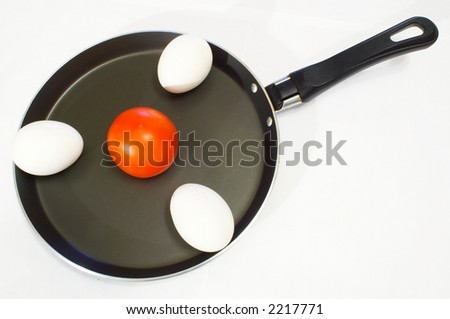 Three white chicken eggs and tomato on a frying pan for an omelette - stock photo