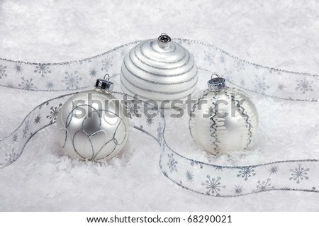 Three white Christmas ornaments with silver ribbon - stock photo
