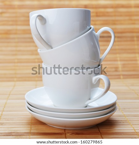 three white coffee cups with saucers on wooden background     white - stock photo
