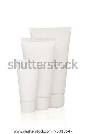 Three white cosmetic bottles stand on a white background - stock photo