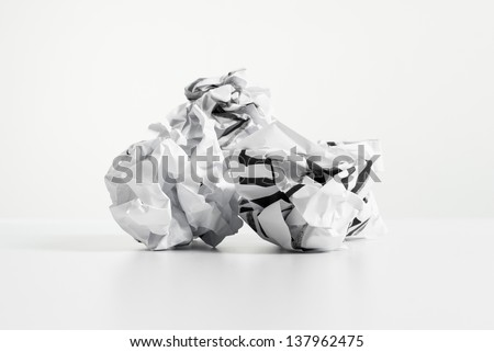 Three white crumpled paper balls over white desk and white background. 404 error page concept. - stock photo