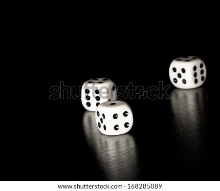 three white dice on old wood black table on black background with space for text - stock photo