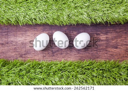 three white easter eggs laying on wooden table top and decorated with green grass