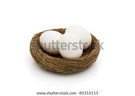 Three white eggs in a nest isolated on a white background