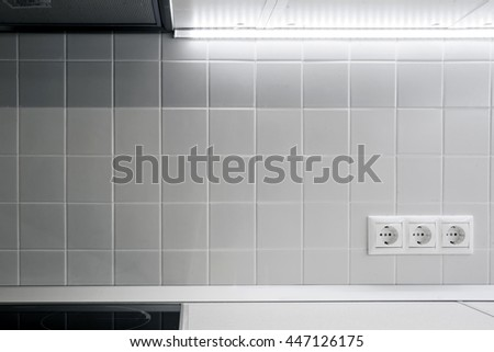 Three white electric socket on the white wall tiles in the kitchen with white backlight