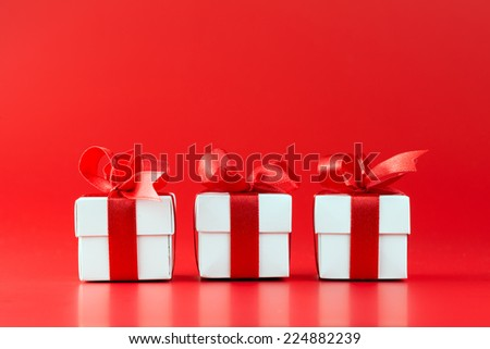 Three white gift boxes with ribbons on red background - stock photo