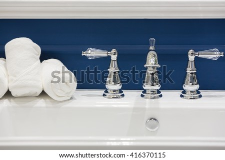 Three white hand towels on a white basin with hot and cold faucets in a clean and classic style bathroom. - stock photo