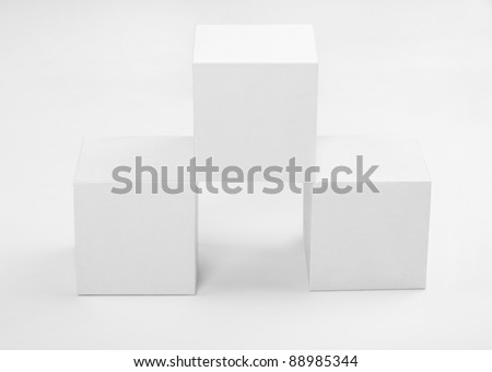three white paper cubes on a gray background - stock photo