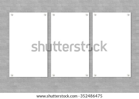 three white poster on brick wall - stock photo