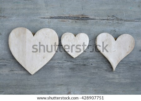 Three white wash hearts hand made of wood on a old grey wooden background with empty copy space