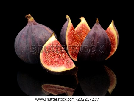 Three whole figs look like flower isolated on black background - stock photo