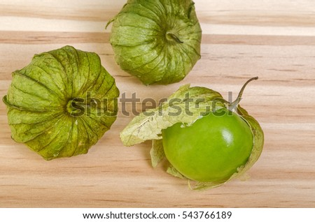 Three Whole Green Husk Tomatoes, one with loose husk, on table