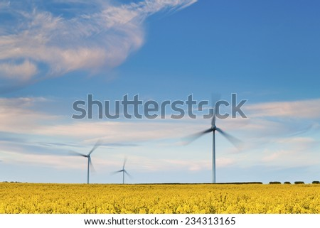 Three Wind Turbines at Yellow Rapeseed Field in Burton Latimer, United Kingdom - stock photo
