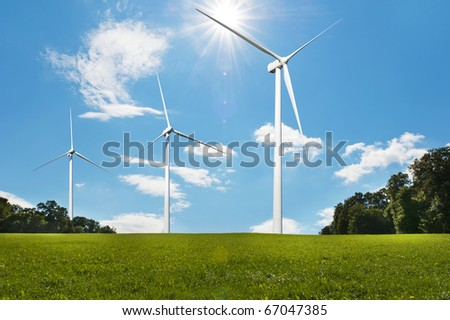 Three wind turbines on a green meadow  generating electricity - stock photo