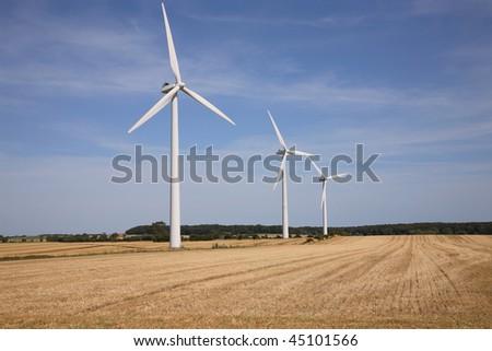 Three wind turbines on a harvested wheat field. - stock photo