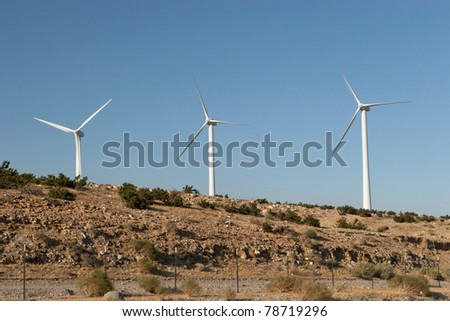 Three wind turbines on a hill against the blue sky / Wind Turbines on a Hill