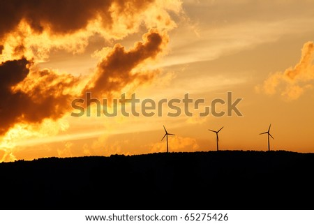 three wind turbines on horizon at sunset - stock photo