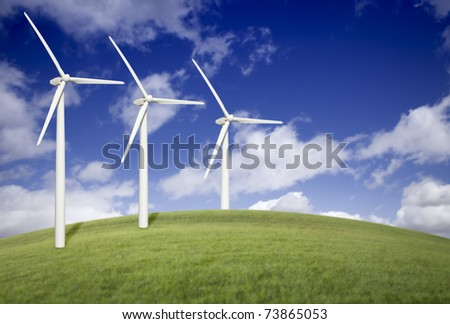 Three Wind Turbines Over Grass Field, Dramatic Blue Sky and Clouds.