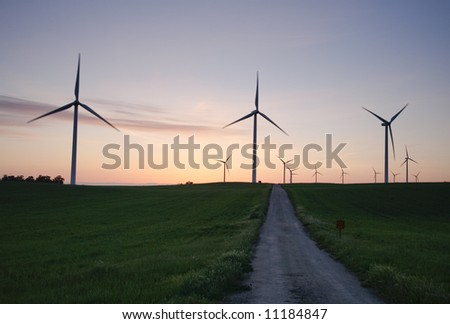 three windmills and a road at dawn