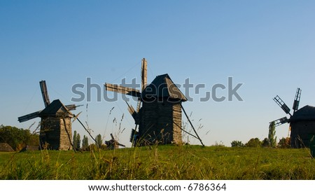 Three windmills in row on autumn's sunset