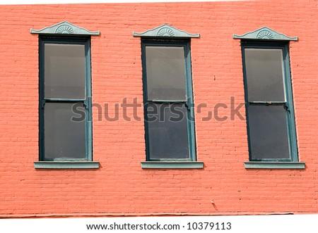 Three windows in a pink brick wall - stock photo