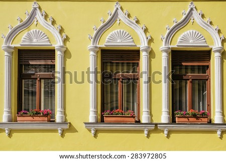 Three Windows of the Old Building on an Yellow Wall - stock photo