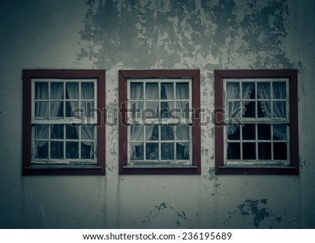 three windows on the shabby wall closed with curtains