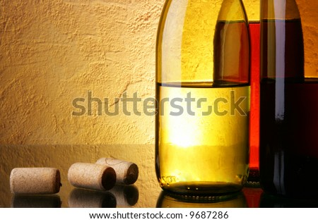 Three wine bottles and corks over textured background with space for text - stock photo