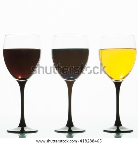 Three wine glasses with colored liquids on a white background.