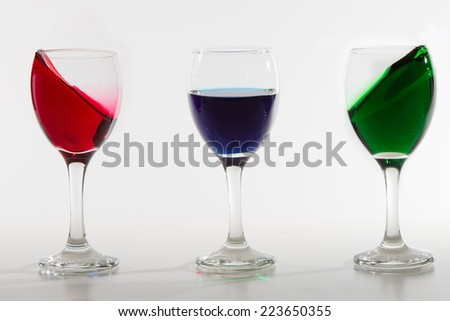 Three wine glasses with colour water spill on a white background with shiny surface