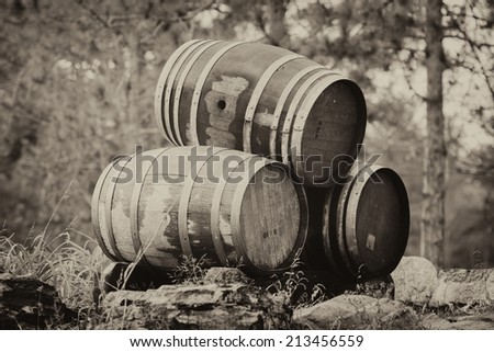 Three wine or whiskey barrels stacked outside on their sides.  Sepia toned for a aged vintage look.  - stock photo