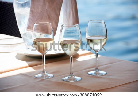 Three wineglasses with cold white wine in outdoor cafe near sea - stock photo
