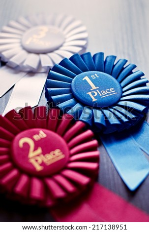 Three winners rosettes for first, second and third place in pleated blue, red and white ribbon respectively with central text - stock photo