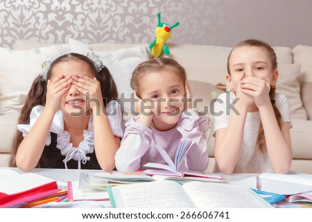 Three wise monkeys. Three small schoolgirls jokingly pretend three wise monkeys closing their eyes, ears and mouth in the meaning of see no evil, hear no evil, speak no evil - stock photo