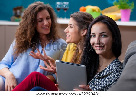 Three woman sitting at home in the couch talking and having fun