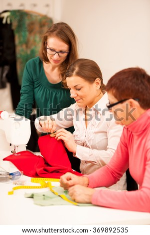 Three women are sewing on handcraft workshop. They are teaching each other of sewing skills.